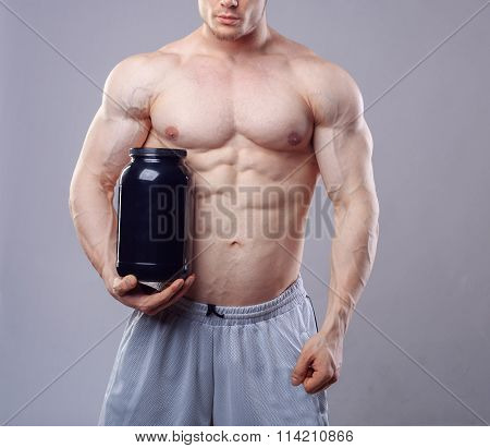 Bodybuilder holding a black plastic jar with whey protein on grey background