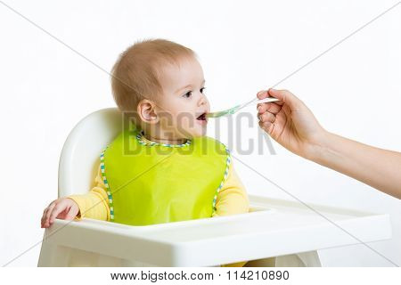 baby eats with spoon sitting in highchair
