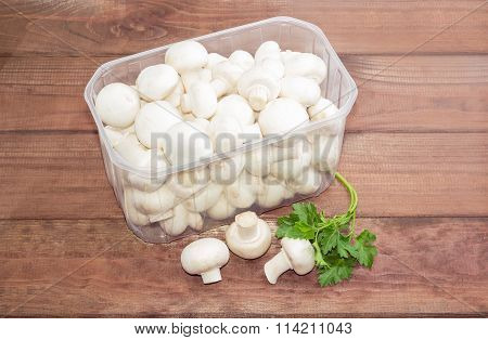 Button Mushrooms In A Plastic Tray On A Wooden Surface
