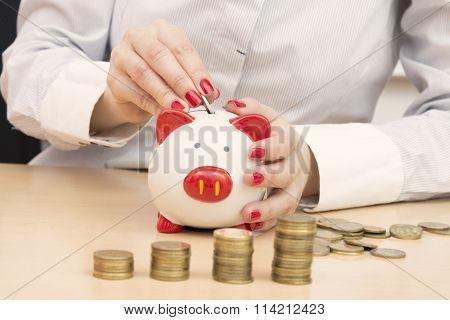 Female hand putting money coin into piggybank slot