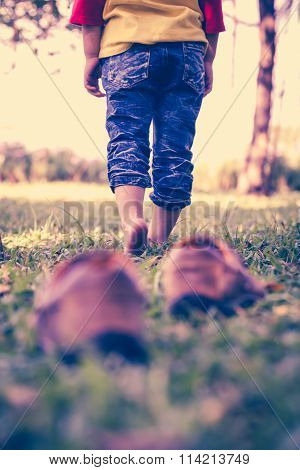 Girl Take Off Her Shoes. Child's Foot Learns To Walk On Grass