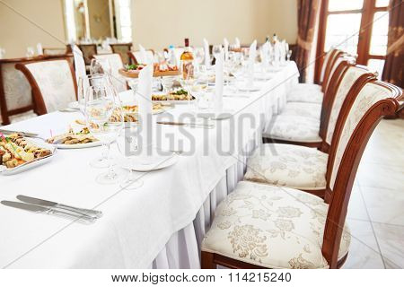 catering table set service with silverware, napkin and glass stemware at restaurant before party