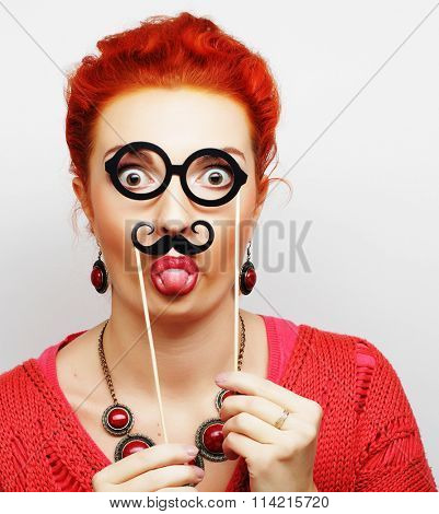 young woman holding mustache and glasses on a stick.