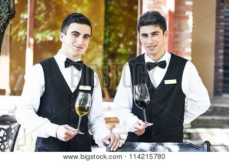 Portrait of two young smiling waiters with glasses of wine at restaurant or cafe
