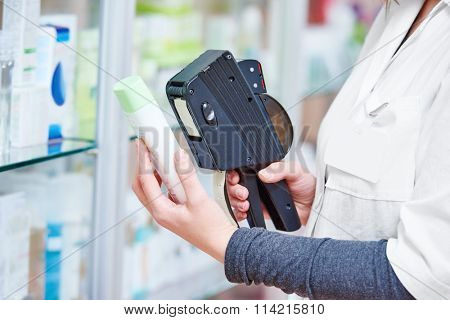 Hand of female pharmacist using labeling gun labeler for sticking price label of medicine in drugstore