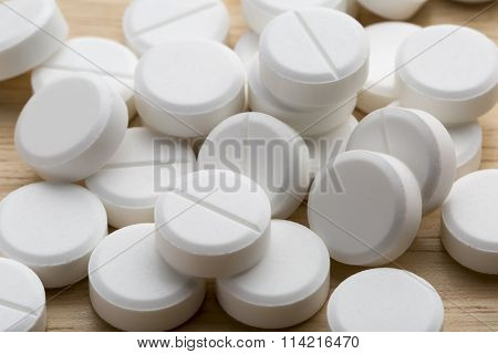 Heap of white round pills on a gray background