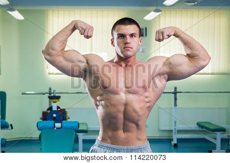 Man at the gym. Man makes exercises dumbbells.