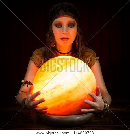 Young Pretty Fortune Teller With A Crystal Ball, Dark Background