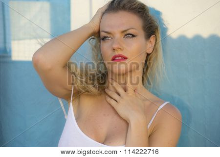 beautiful blond woman in lingerie on a terrace by the sea in summer