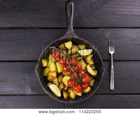Frying Pan With Fried Potato And The Baked Cherry Tomatoes On Branch, Segments Of Lime And Fork On A