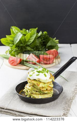 Zucchini Fritters With Sour Cream On Frying Pan, Various Vegetables On White Background