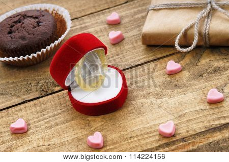 Condom in a gift box and chocolate muffin
