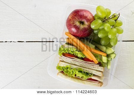 Lunchbox With Sandwich, Vegetables, Fruit On White Background. Top View