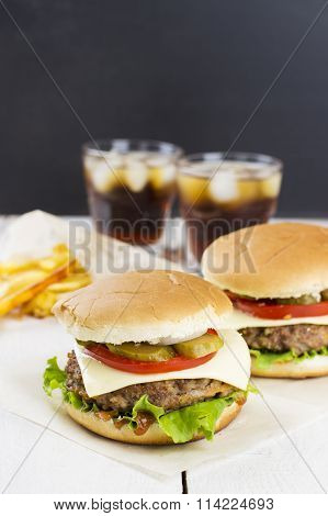 Mini Burger With Vegetables And Meat, French Fries And Drink On A White Wooden Background