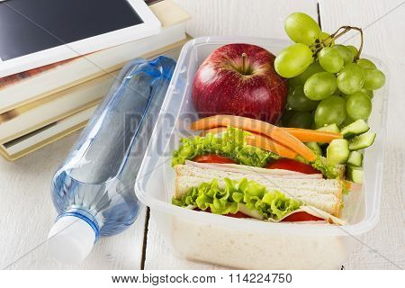 Lunchbox With Sandwich, Vegetables And Fruit, Bottle Of Water And Pad On A White Background