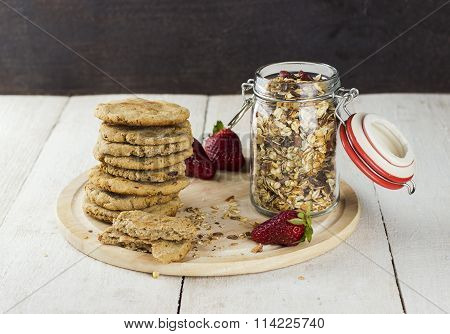 Granola With Nuts In A Glass Jar, Strawberry, A Pile Of Oatmeal Cookies And The Crumbled Cookies On