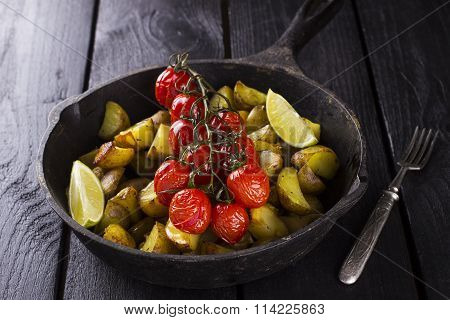 Frying Pan With Fried Potato And The Baked Cherry Tomatoes On Branch, Lime Segments And Fork On A Wo