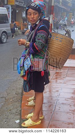 woman with basket is walking on the street in Sa Pa, Vietnam