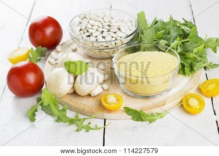 Ingredients For Couscous With Haricot, Mushrooms, Arugula And Tomatoes On A Wooden Background