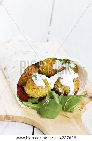 Falafel In Wheat Tortilla With Tomatoes, Arugula On A White Wooden Background