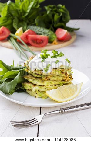 Zucchini Fritters On White Plate With Sour Cream, Sorrel And Lemon On White Background