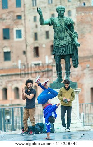 ROME ITALY - NOVEMBER 22 2015: Boys practice street dance under the statue of Julius Caesar in Rome Italy November 22 2015.