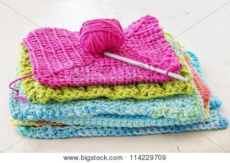 Crocheted dishcloths, with a hook and a ball of yarn.