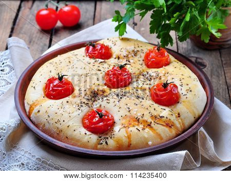 Homemade focaccia with cherry tomatoes, sea salt and herbs in a clay bowl on a gray wooden backgroun