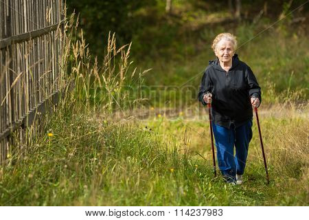 An elderly woman practices Nordic walking in the Park.