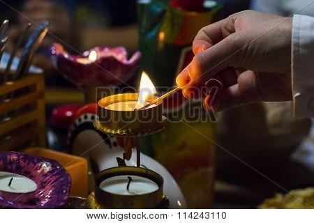 background blurred woman's hand lights a candle in a candlestick with a match