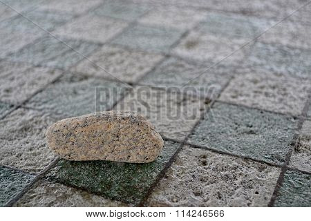 Small Rock on Chessboard Table