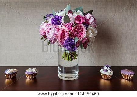 bridal bouquet of peonies in a vase and cupcakes