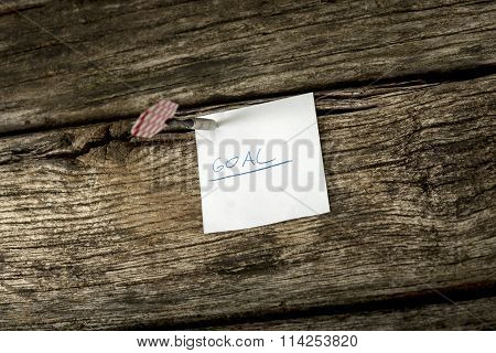 White Piece Of Paper With The Word Goal Pinned To A Rustic Wooden Boards With A Dart