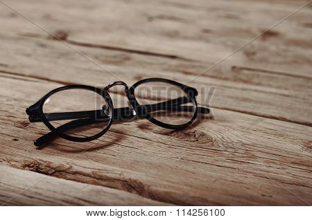 Black Reading Glasses On Wooden Background