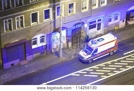 An Ambulance With Flashing Lights Standing In Front Of A Building At Night.