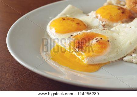 Fried Eggs Closeup On A White Plate