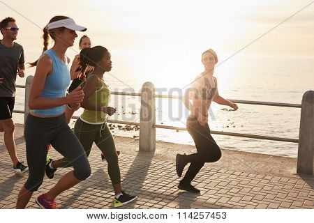 Young People Running Along Seaside At Sunset