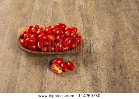 A Bowl Of Grape Tomatoes Over A Wood Table