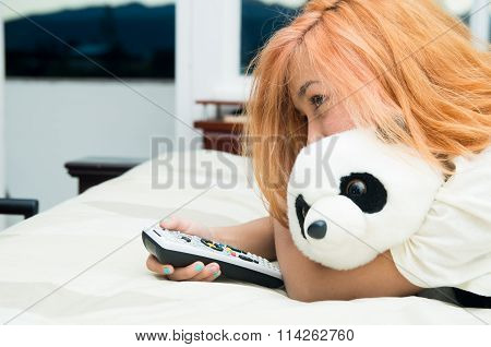 Pretty young woman lying comfortably on bed hugging stuffed panda animal and pressing remote control