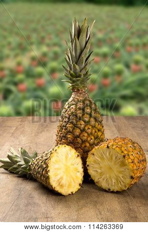 Some Pineapples Over A Wooden Table