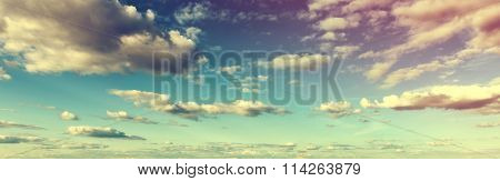 Atmospheric toned panoramic skyscape with colorful clouds at sunset or sunrise in a nature or weather banner