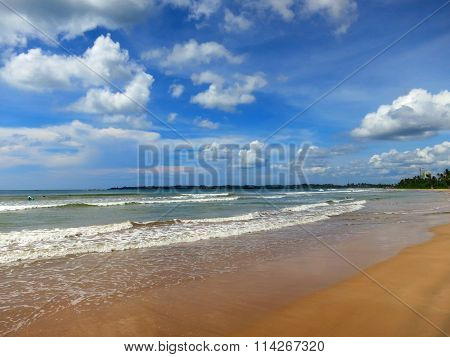 Calm tropical beach with white sand and turquoise water under blue cloudy sky