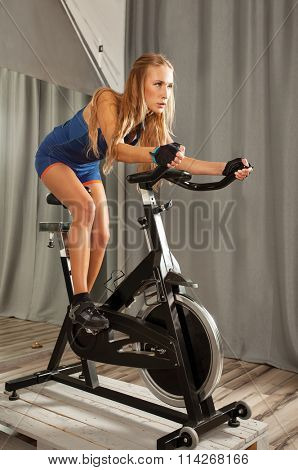 Young beautiful woman doing exercise on a spinning machine in a cycling gym.
