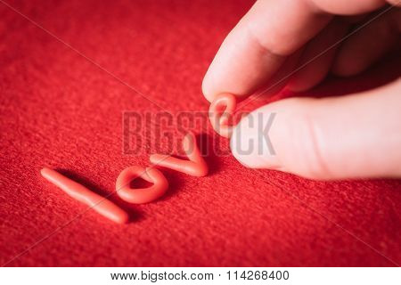 Man wrote word love with red letters on a red background. Valentines Day