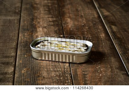 an open sardine can on a rustic wooden surface