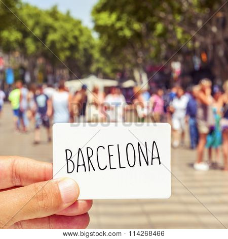 closeup of the hand of a young man showing a signboard with the word Barcelona, at the famous Las Ramblas in Barcelona, Spain