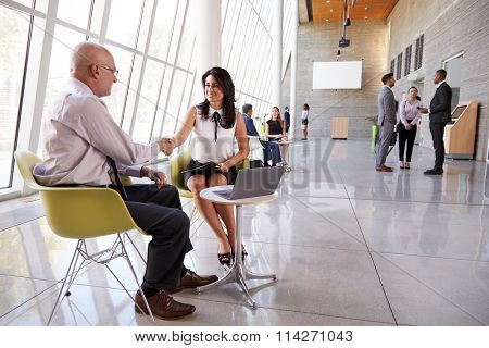 Business Meeting In Busy Office Foyer Area