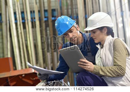 Engineers in metallurgy warehouse using digital tablet