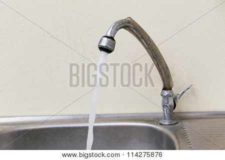 Faucet With Water Flowing.
