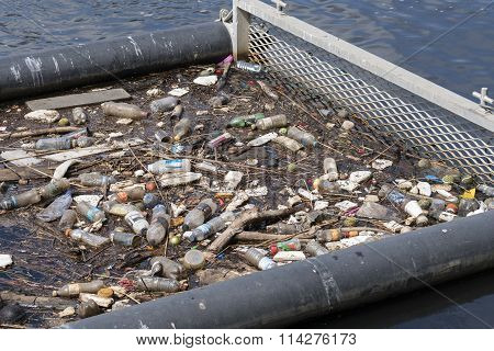 Litter trap with rubbish floating on water